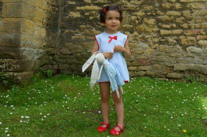 Niña posando en un jardin con un muñeco vestida con jesusito de rayas azules y blanco, y detalles en rojo.