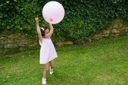 Niña jugando vestida con jesusito rosa rayas jugando en un jardin con un globo.