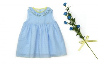Exposición vestido plumeti azul con detalles en amarillo y ramo de flores azules.