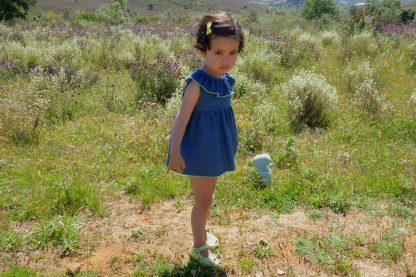 Niña posando en prado vestida con conjunto vaquero azul oscuro y amarillo.