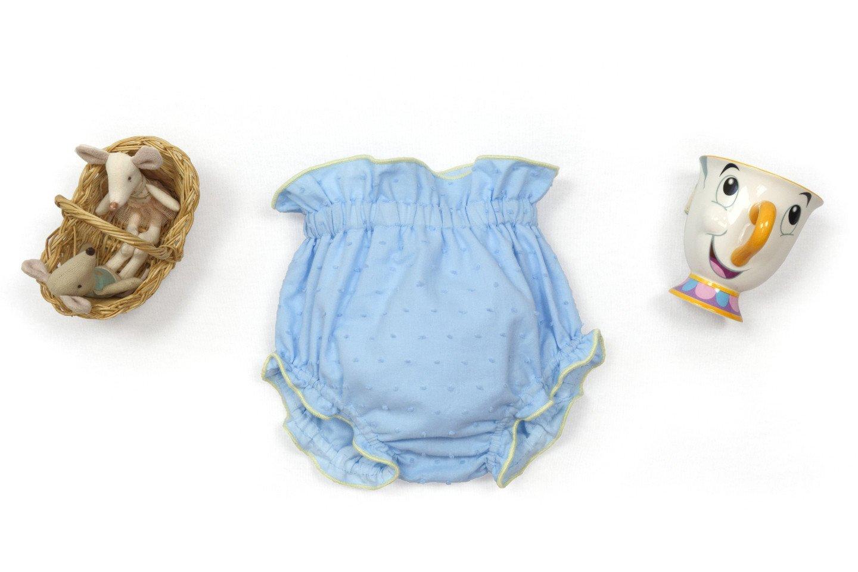 Exposición de culotte plumeti azul con cesto de ratoncitos y taza con cara.