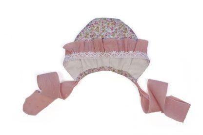 Vista frontal capota estampada flores tonos rosa con detalles volante y puntilla.
