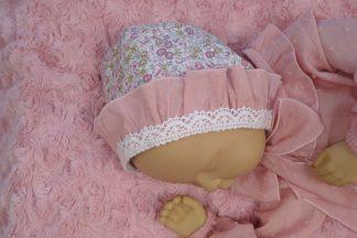 Vista lateral maniqui bebé con caporta Peonias y camisa plumeti rosa.