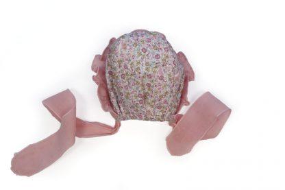 Vista trasera capota estampada flores tonos rosa con detalles de volante y puntilla.