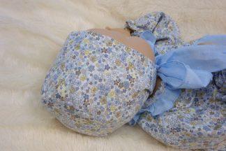 Vista lateral de maniqui bebe con capota de flores azul.