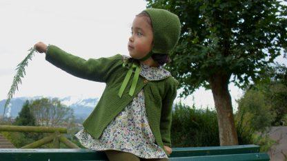 Niña en paisaje otoñal vestida con jesusito estampado en tonos verde, terracota y marinos.