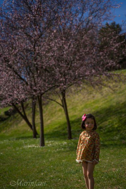 Niña posando en jardines con jesusito liberty flores amapola, fucsia, azul y verde.