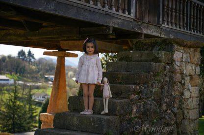 Niña posando en horreo asturiano con jesusito rayas arena y rosa.