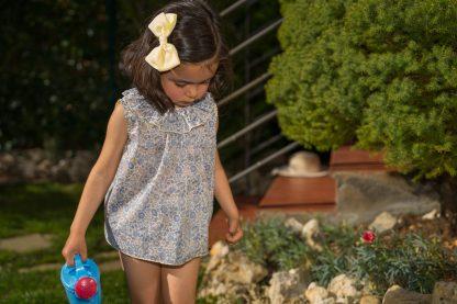 Niña en jardín vestida con blusa flores liberty tonos azules y amarillo con culotte a juego y lazo amarillo en el pelo.