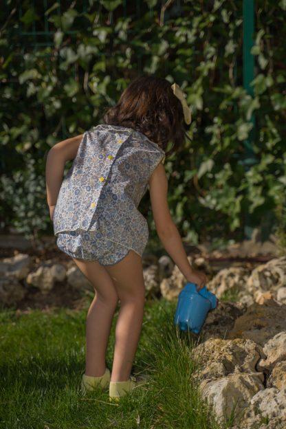 Niña en jardín regando vestida con blusa flores liberty tonos azules y amarillo con culotte a juego.