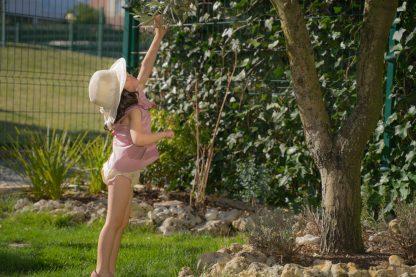Niña en jardín vestida con camisa sin mangas rosa y culotte de flores liberty al tono.